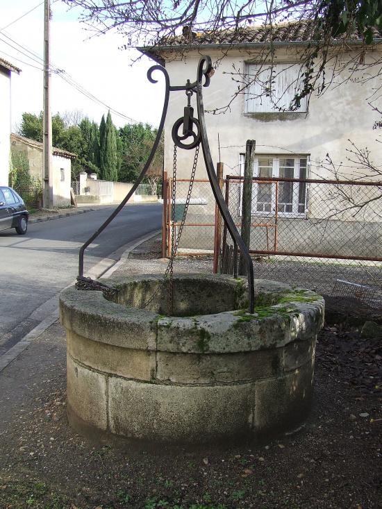 Génissac, un puits avec treuil, support et chaine de levage.